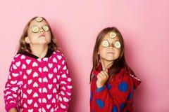 Enfants avec les visages sérieux, concombres sur des yeux et cheveux lâches photos libres de droits