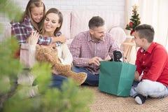 Enfants avec leurs cadeaux de Noël photographie stock