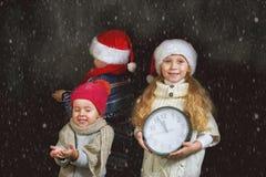 Enfants avec une horloge et un chapeau de Noël sur un fond foncé Image stock