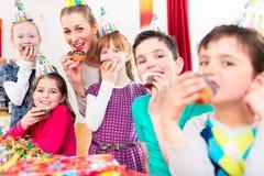 Enfants ayant des petits gâteaux célébrant l'anniversaire Photos stock
