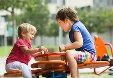Enfants ayant l'amusement au terrain de jeu Image libre de droits