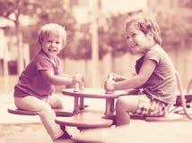 Enfants ayant l'amusement au terrain de jeu Photo stock