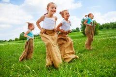 Enfants ayant l'amusement avec des sacs sur un pré Image libre de droits