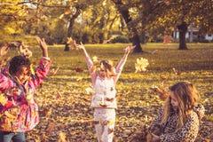 Enfants ayant l'amusement avec les feuilles tombées Photos libres de droits