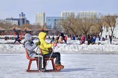 Enfants ayant l'amusement avec sledging sur la glace dans le parc de Nanhu, Tchang-tchoun, Chine Photo stock