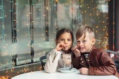Enfants ayant l'amusement en café extérieur Images libres de droits