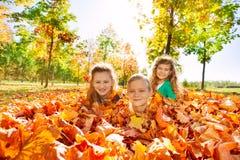 Enfants ayant l'amusement s'étendant au sol avec des feuilles Image libre de droits