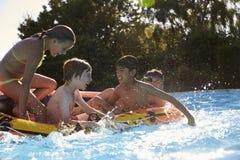 Enfants ayant l'amusement sur gonflable dans la piscine extérieure Photographie stock
