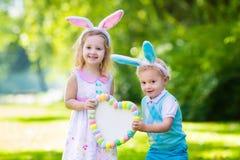 Enfants ayant l'amusement sur la chasse à oeuf de pâques Photo libre de droits