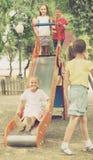 Enfants ayant l'amusement sur la glissière au terrain de jeu Photo libre de droits