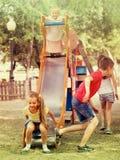 Enfants ayant l'amusement sur la glissière au terrain de jeu Images libres de droits