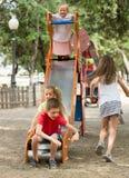 Enfants ayant l'amusement sur la glissière au terrain de jeu Image libre de droits