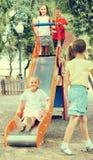 Enfants ayant l'amusement sur la glissière au terrain de jeu Photo stock