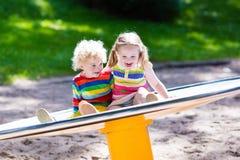 Enfants ayant l'amusement sur un terrain de jeu Photographie stock libre de droits