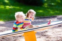 Enfants ayant l'amusement sur un terrain de jeu Image libre de droits