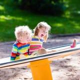 Enfants ayant l'amusement sur un terrain de jeu Photos stock