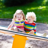 Enfants ayant l'amusement sur un terrain de jeu Photo stock