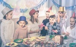 Enfants ayant la célébration de l'anniversaire de friend's pendant le dîner Photos stock