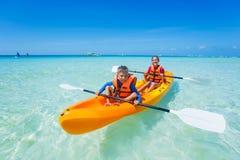 Enfants barbotant dans le kayak photos stock