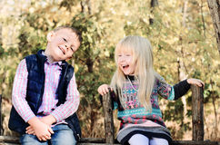 Enfants blancs heureux s'asseyant sur la barrière en bois de jardin Images stock