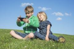 Enfants blonds heureux à l'aide du smartphone (jeu de observation de film ou de jouer) se reposant sur l'herbe Photographie stock