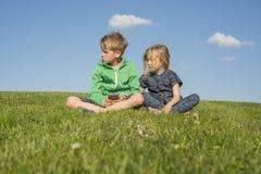 Enfants blonds heureux à l'aide du smartphone (jeu de observation de film ou de jouer) se reposant sur l'herbe Images libres de droits