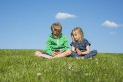 Enfants blonds heureux à l'aide du smartphone (jeu de observation de film ou de jouer) se reposant sur l'herbe Photographie stock libre de droits