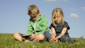 Enfants blonds heureux à l'aide du smartphone (jeu de observation de film ou de jouer) se reposant sur l'herbe banque de vidéos