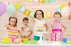 Enfants c?l?brant la f?te d'anniversaire Les enfants heureux montrent des pouces  images libres de droits