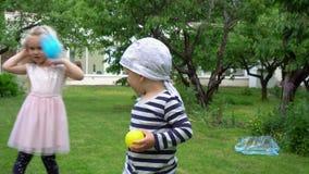Enfants caucasiens avec les boules de lancement de mère dans la caméra Mouvement de cardan banque de vidéos