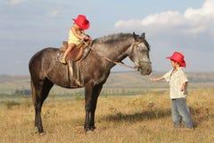 Enfants chez le cheval d'équitation de chapeau de cowboy à l'extérieur Image stock
