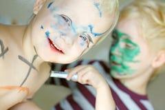 Enfants colorant leurs visages avec des marqueurs image libre de droits