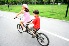 Enfants conduisant sur un vélo tandem. Photos stock