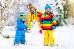 Enfants construisant le bonhomme de neige Enfants dans la neige Amusement de l'hiver Photographie stock libre de droits
