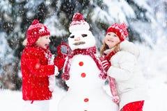 Enfants construisant le bonhomme de neige Enfants dans la neige Amusement de l'hiver Images stock