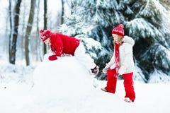 Enfants construisant le bonhomme de neige Enfants dans la neige Amusement de l'hiver Image stock