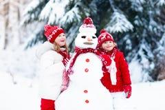 Enfants construisant le bonhomme de neige Enfants dans la neige Amusement de l'hiver Images libres de droits
