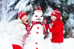 Enfants construisant le bonhomme de neige Enfants dans la neige Amusement de l'hiver Photo stock
