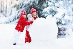 Enfants construisant le bonhomme de neige Enfants dans la neige Amusement de l'hiver Photographie stock
