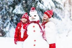 Enfants construisant le bonhomme de neige Enfants dans la neige Amusement de l'hiver Photo libre de droits