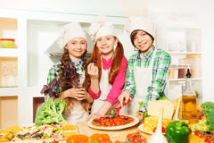 Enfants coupant la pizza italienne traditionnelle à la cuisine Image stock