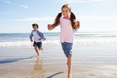 Enfants courant à partir des vagues de rupture sur la plage images stock