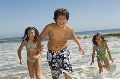 Enfants courant dans l'eau à la plage Photo stock
