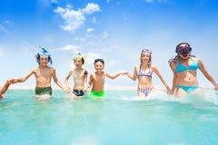Enfants courant en mer tenant ensemble des mains Photographie stock libre de droits
