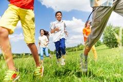 Enfants courants jouant ensemble dehors Image stock