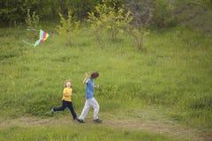 Enfants courus jouant le cerf-volant sur le pré d'été Images stock