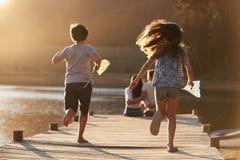 Enfants courus vers des parents sur la jetée en bois par le lac image libre de droits
