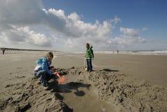 Enfants creusant à la plage Photographie stock libre de droits