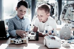 Enfants décontractés construisant les machines robotiques avec des sourires sur leurs visages Photographie stock