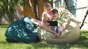 Enfants décontractés passant le temps avec le comprimé banque de vidéos